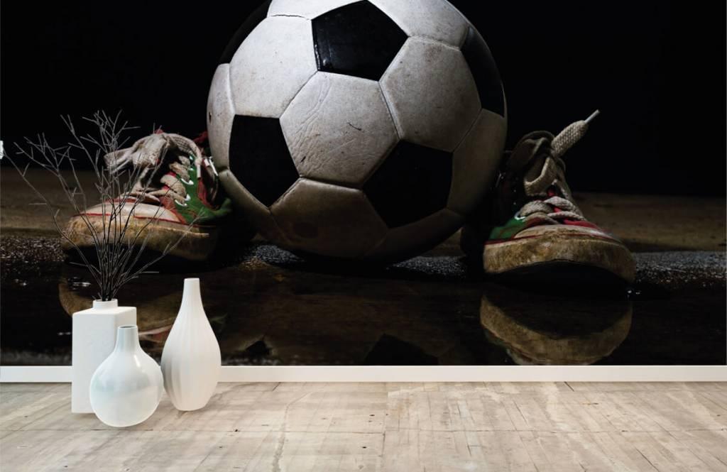 Fotboll tapet Fotboll mellan två sneakers 1